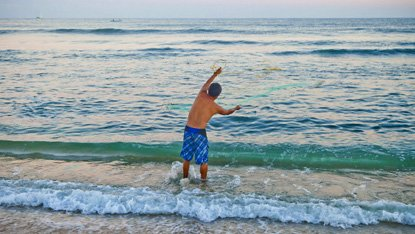 A fisherman flings his net into the shorebreak