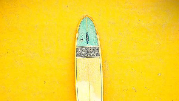 -en-a-lone-longboard-on-a-yellow-wall-es-tabla-larga-solitaria-sobre-una-pared-amarilla-