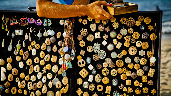 -en-a-beach-vendor-offers-carved-stone-pendants-es-vendedor-playero-ofreciendo-pendientes-de-roca-tallada-