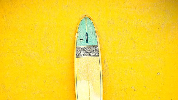 -en-a-lone-longboard-on-a-yellow-wall-es-tabla-larga-solitaria-sobre-una-pared-amarilla-