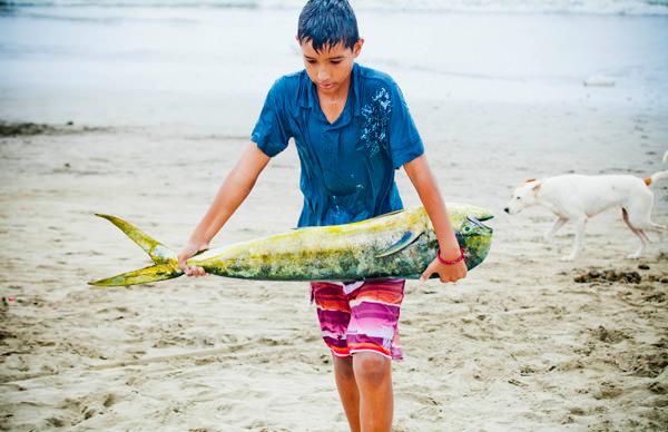 -en-a-boy-brings-a-fish-to-market-es-nio-llevando-pescado-al-mercado-