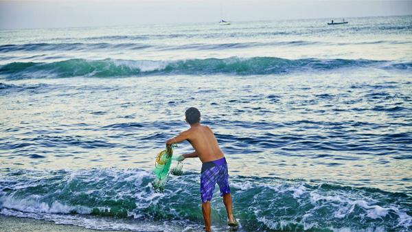 -en-a-fisherman-poised-to-fling-his-net-into-the-waves-es-pescador-listo-para-arrojar-la-red-a-las-olas-